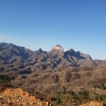 View of Los Picachos de Sinaloa, looking northerly from the drill station of DH-BRG-008.  The bedded rocks are part of the Oligocene or Miocene SMO rhyolitic volcanic field.  The forest covers rocks of Laramide and older age.